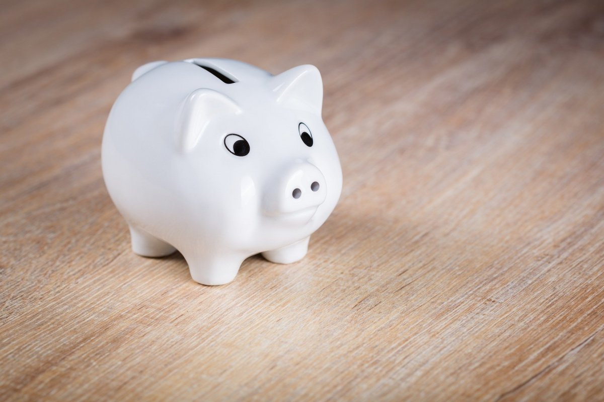Photograph of a piggy bank sitting on a wooden table.