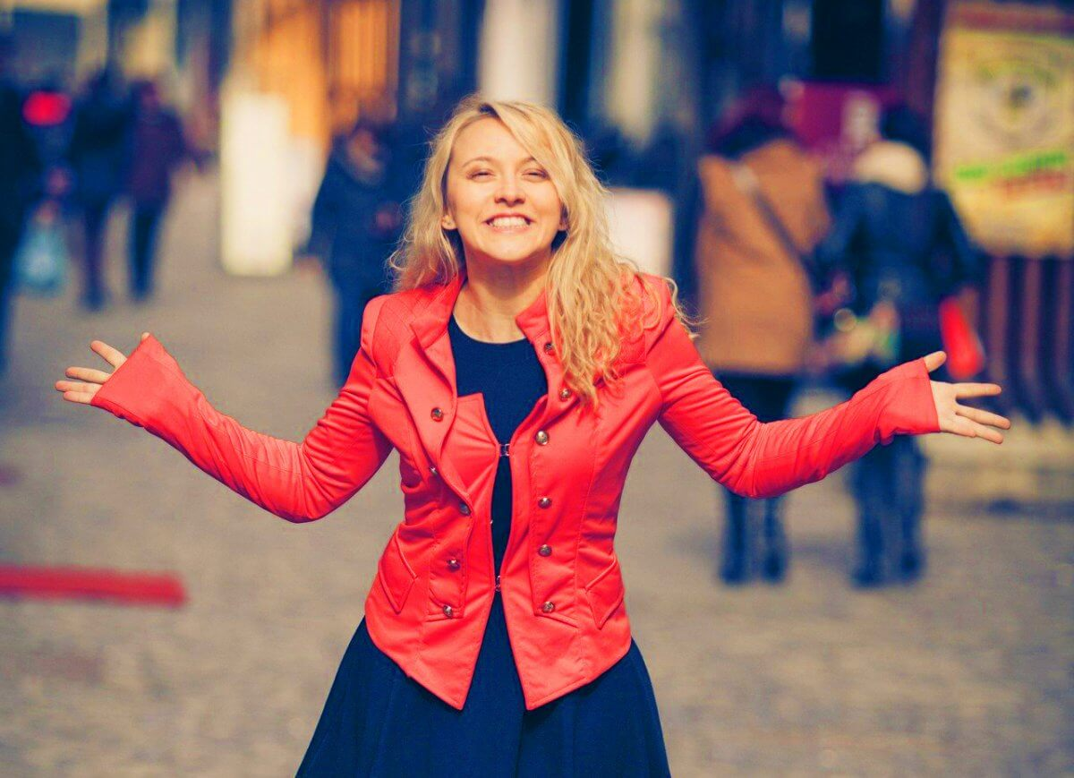 Photograph of a blonde woman wearing a red jacket smiling with both of her hands up outdoors.