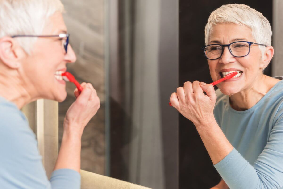 elderly woman brushing teeth